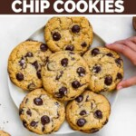 A child's hand reaches toward a plate of chocolate chip cookies.