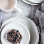 A superfood morning scuffin resting on two stacked plates of varying sizes ready to be served with a mug of hot chai tea. This nutritious baked morning treat is not quite a scone, and not quite a muffin. It's a scuffin.