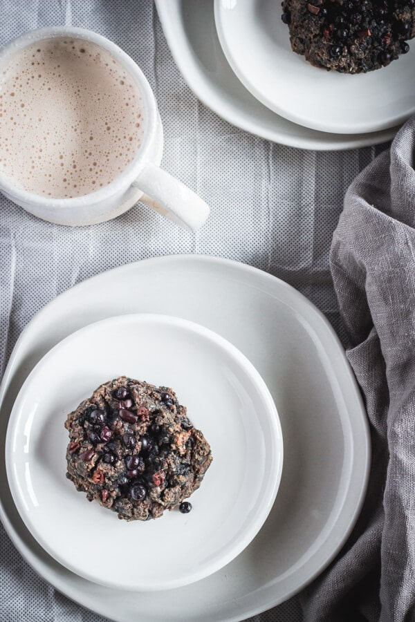 A superfood morning scuffin on resting on two stacked plates of varying sizes ready to be served with a mug of hot chai tea. This nutritious baked morning treat is not quite a scone, and not quite a muffin. It's a scuffin.