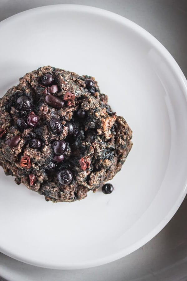 A close-up of a superfood morning scuffin topped with wild blueberries and cacao nibs.