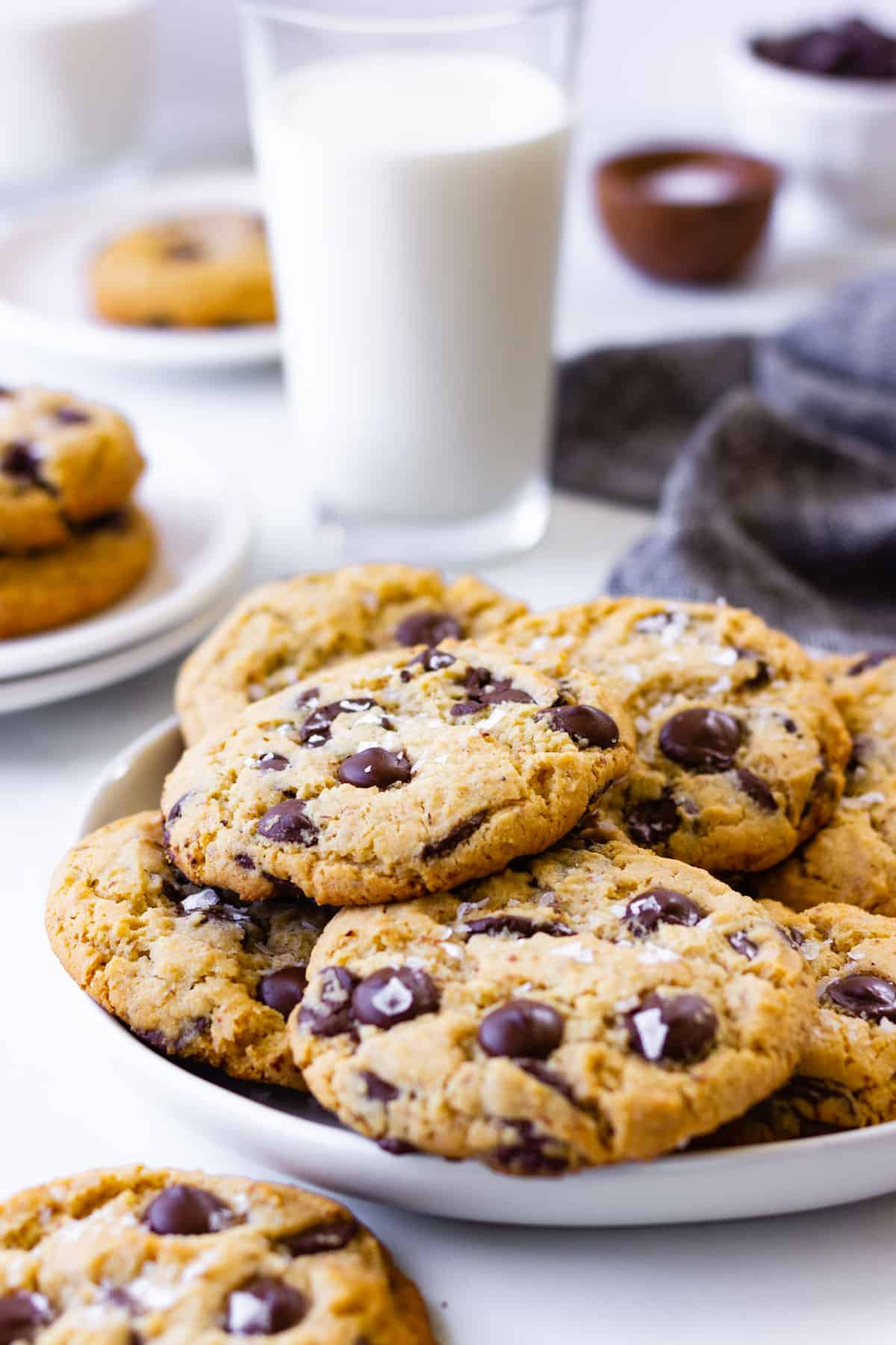 A plate full of cookies with a glass of milk.