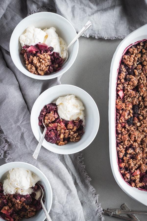 A large baking dish of healthier blackberry apple hazelnut crisp alongside two bowls of the crisp served with vanilla ice cream.