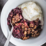 A close-up view of a bowl of blackberry apple hazelnut crisp with a scoop of vanilla ice cream nestled in.