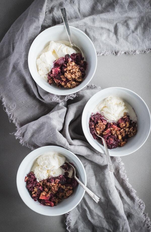 Three bowls of the blackberry apple hazelnut crisp served with vanilla ice cream.