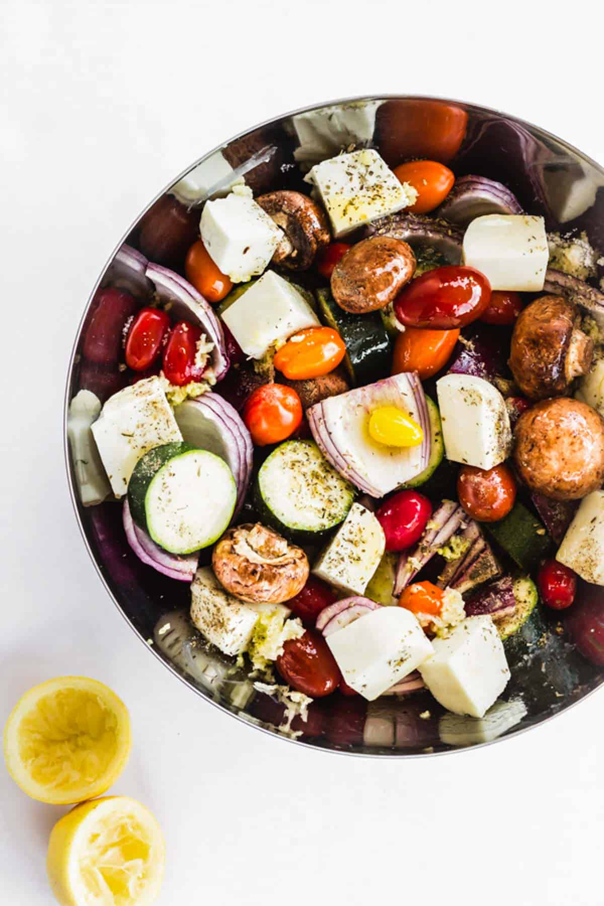 A large bowl of veggies and Halloumi cheese marinating in olive oil, lemon, and herbs.