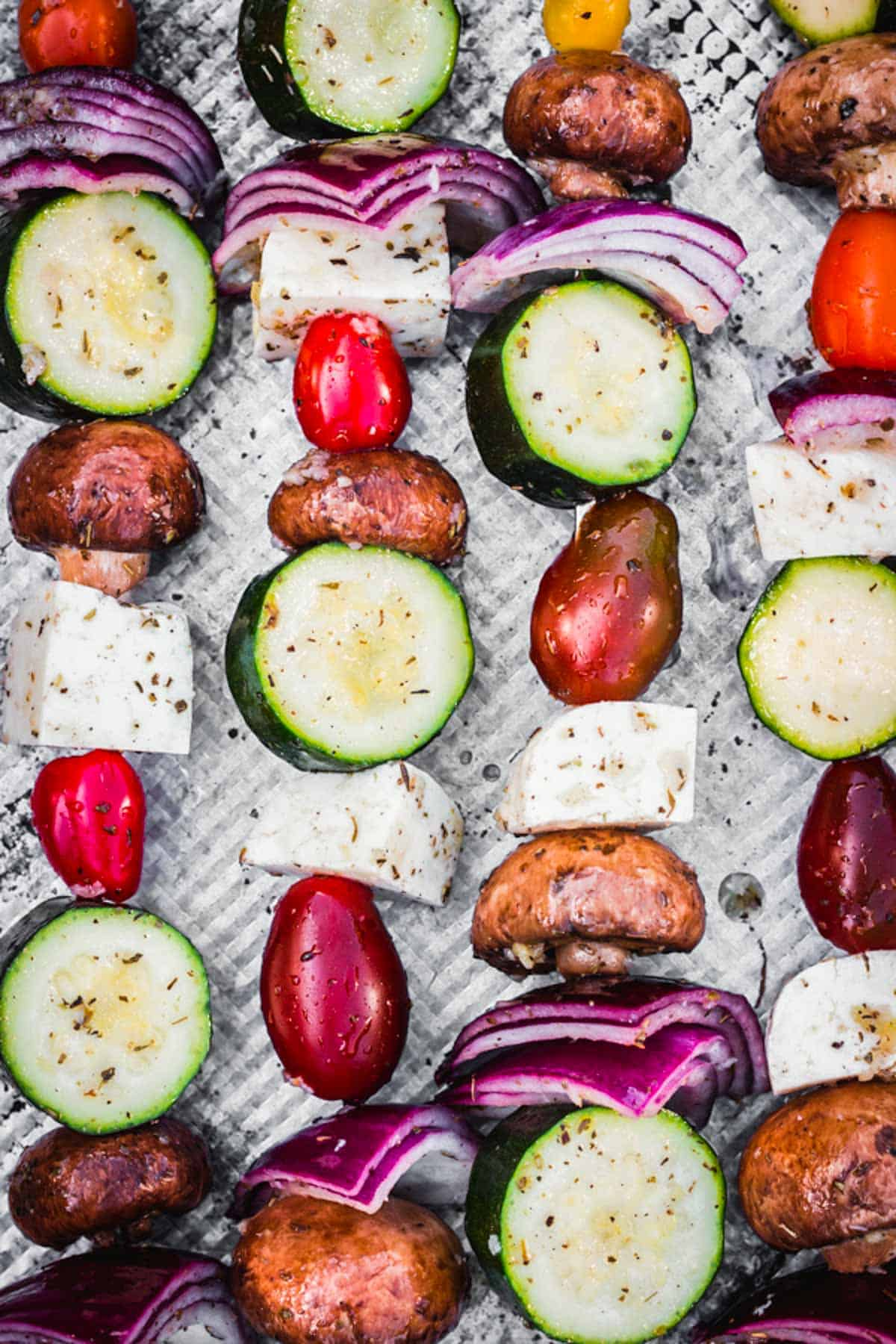 A close-up of veggies and Halloumi cheese on skewers ready to be grilled.