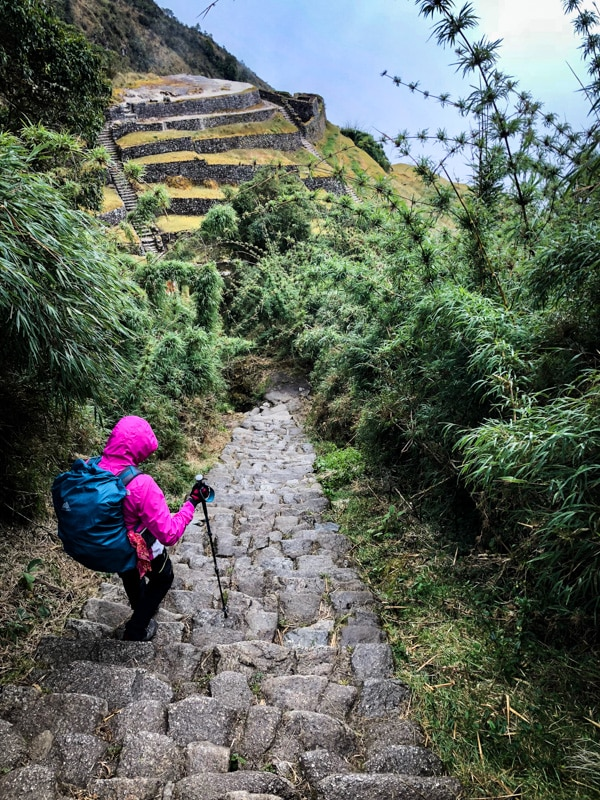 Descending a giant stone stepped staircase. Ancient Incan ruins in the background along the cliffside.