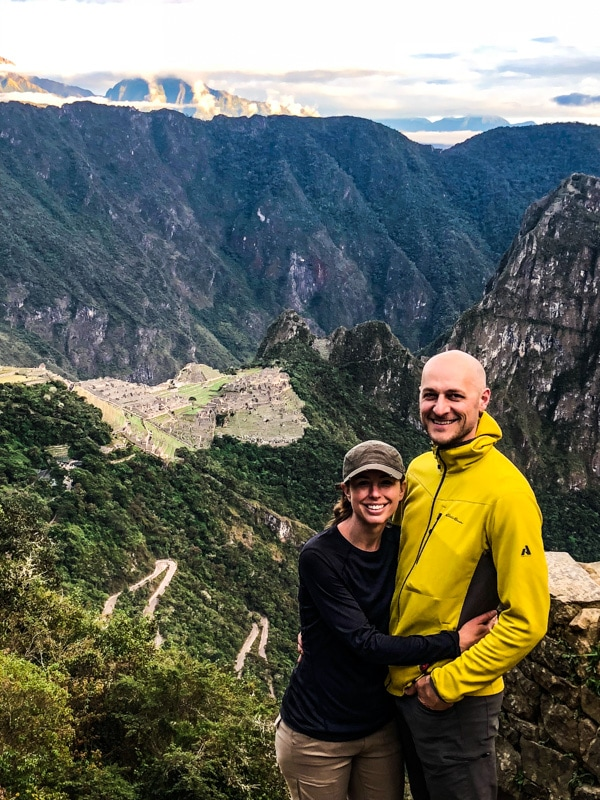 Standing on a cliffside in front of Machu Picchu.