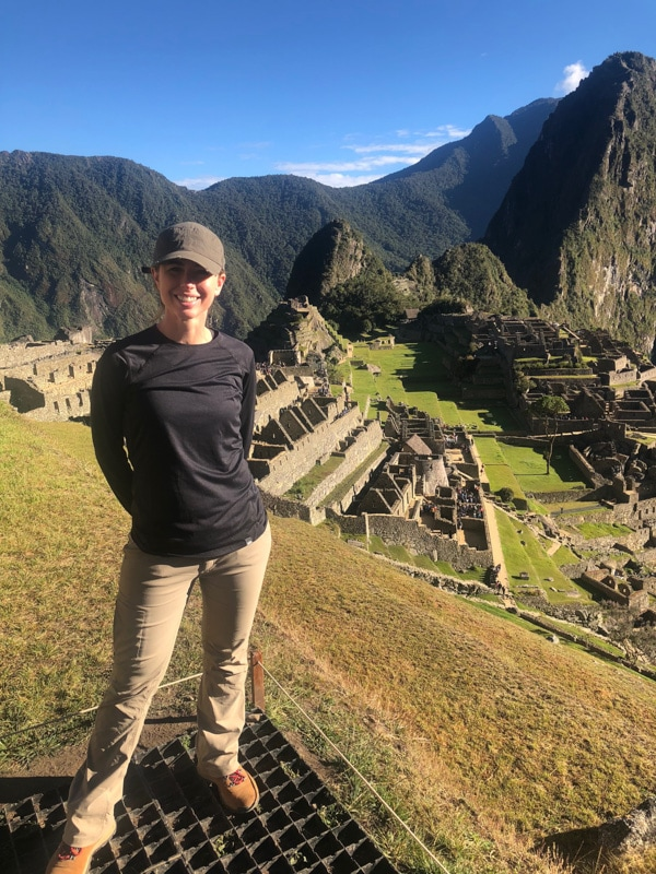 Shannon of Pass Me Some Tasty standing in front of the Machu Picchu ruins.