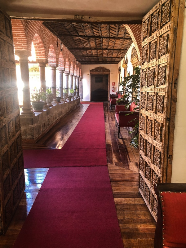 A beautiful corridor with brick arches and ornate wooden doors in The Hotel Marqueses in Cusco, Peru.