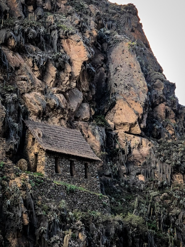 An ancient stone house built alongside a steep cliffside in Ollantaytambo.