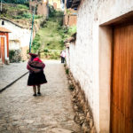 A woman in her Quechuan clothing walking down a stone cobbled road.