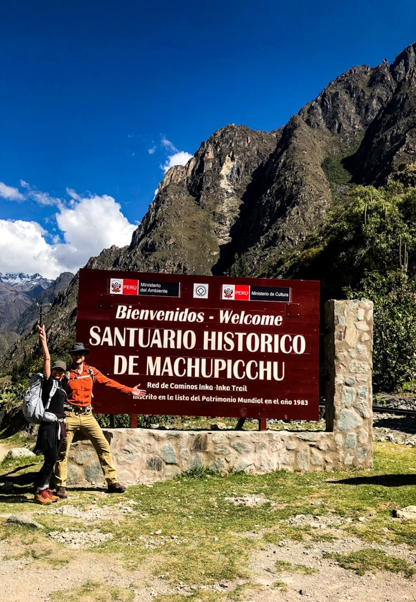 Shannon of Pass Me Some Tasty and her husband standing next to a welcome sign to the Historic Sanctuary of Machu Picchu