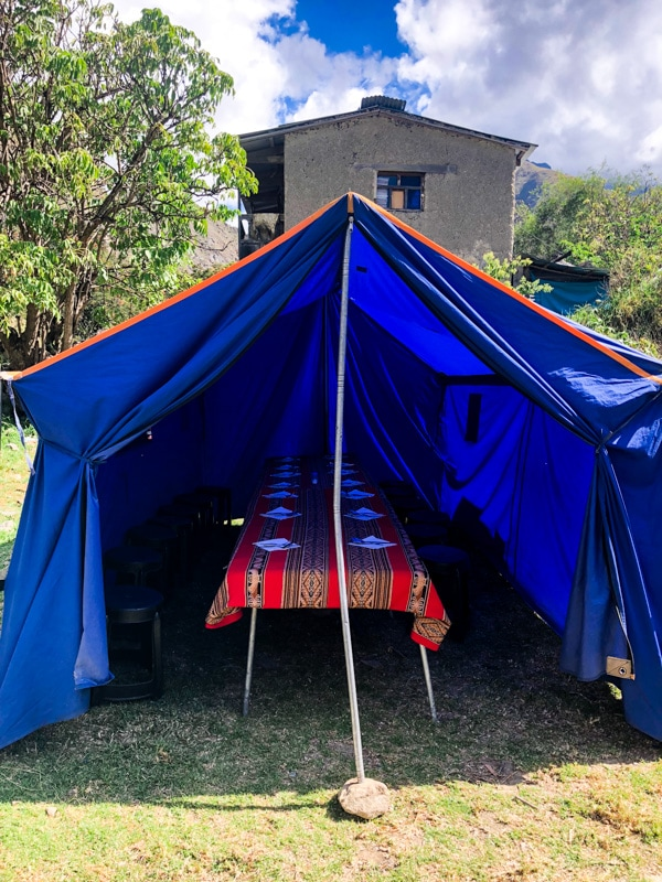 "A blue tent ""dining room"" set up and ready for mealtime."