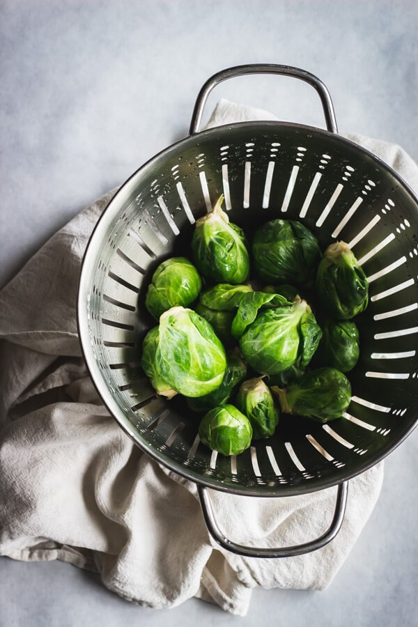 Brussels sprouts rinsed and resting in a colander.
