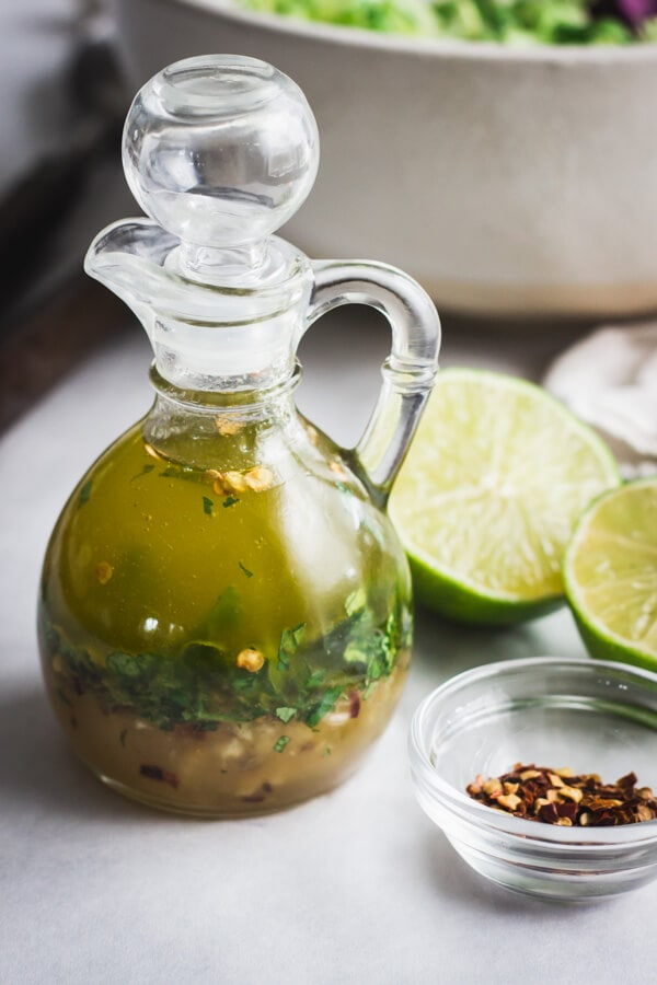 A small glass pouring jar with chili lime vinaigrette. A pinch bowl of red chili flakes and a few lime halves rest nearby.