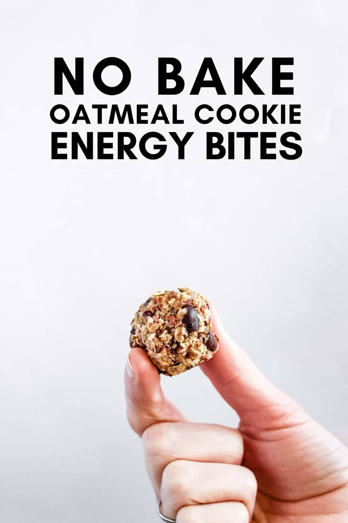 A hand hold ups a no bake oatmeal cookie energy bite against a white background.