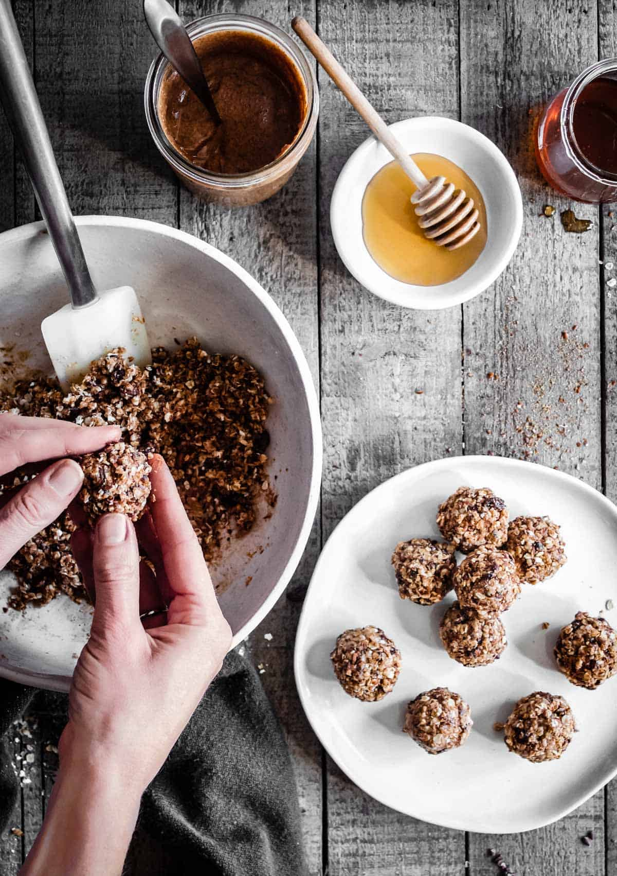 Two hands are forming combined ingredients into no bake oatmeal cookie energy bites.
