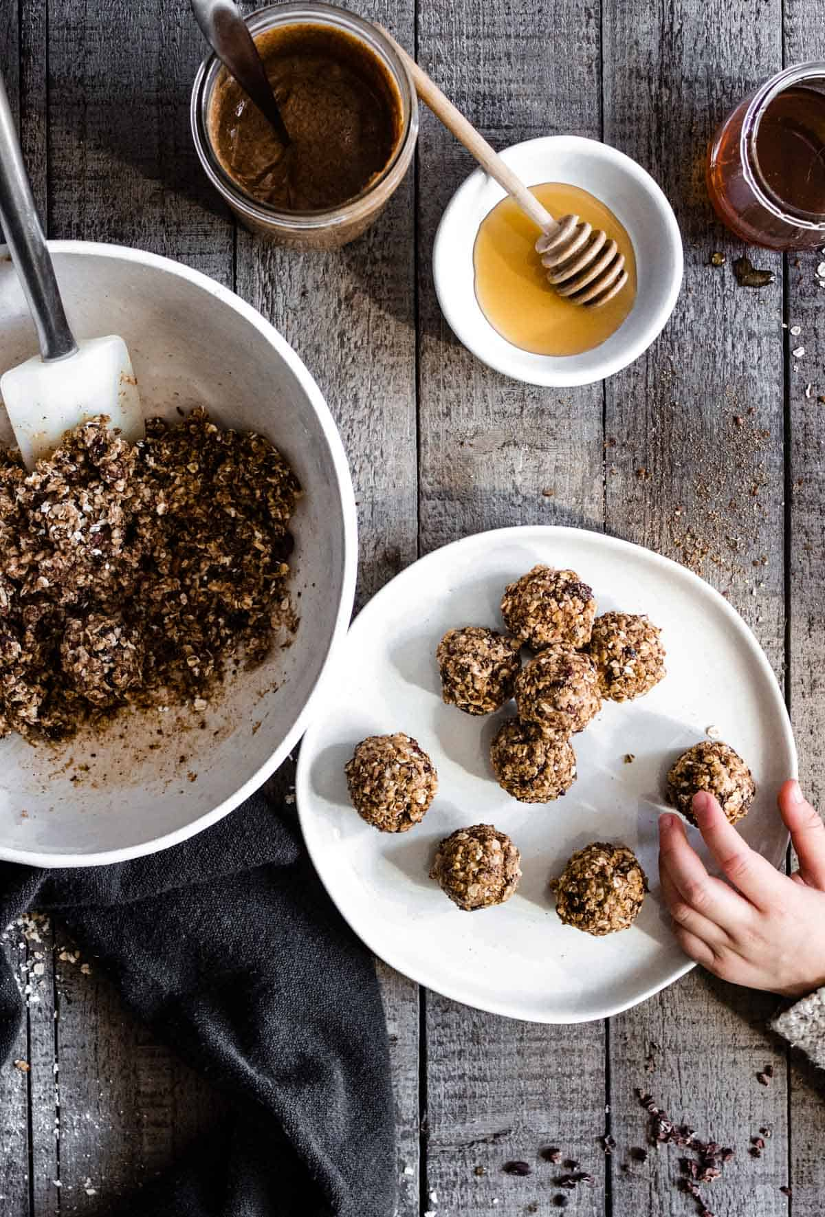 A child's hand is reaching toward a plate of no bake oatmeal cookie energy bites. Ingredients for the bites are placed nearby.