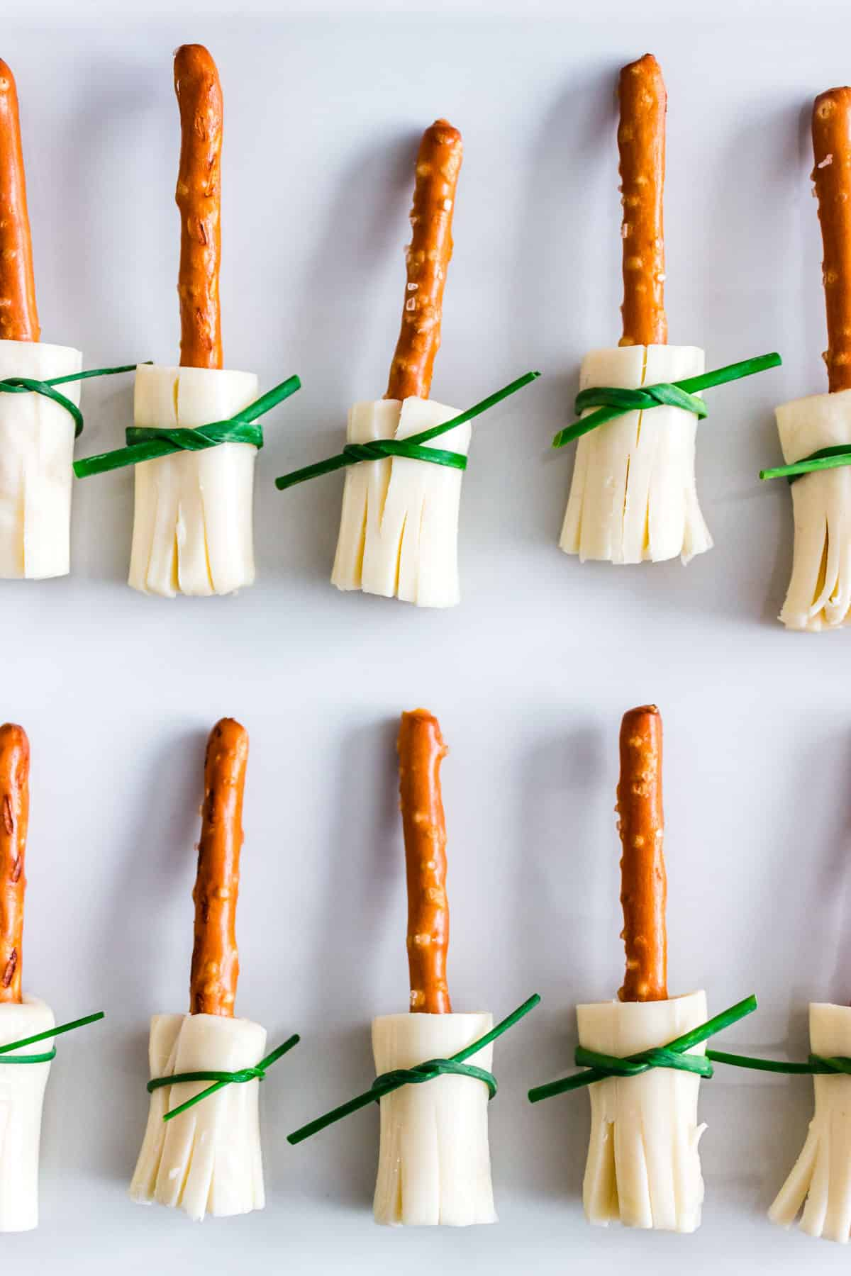 Little broomsticks made with pretzel sticks, string cheese, and chives.