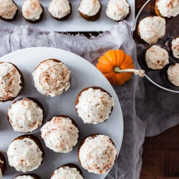 The most delicious pumpkin cupcakes with cream cheese frosting and lightly sprinkled with cinnamon arranged on varied cake plates and serving dishes.