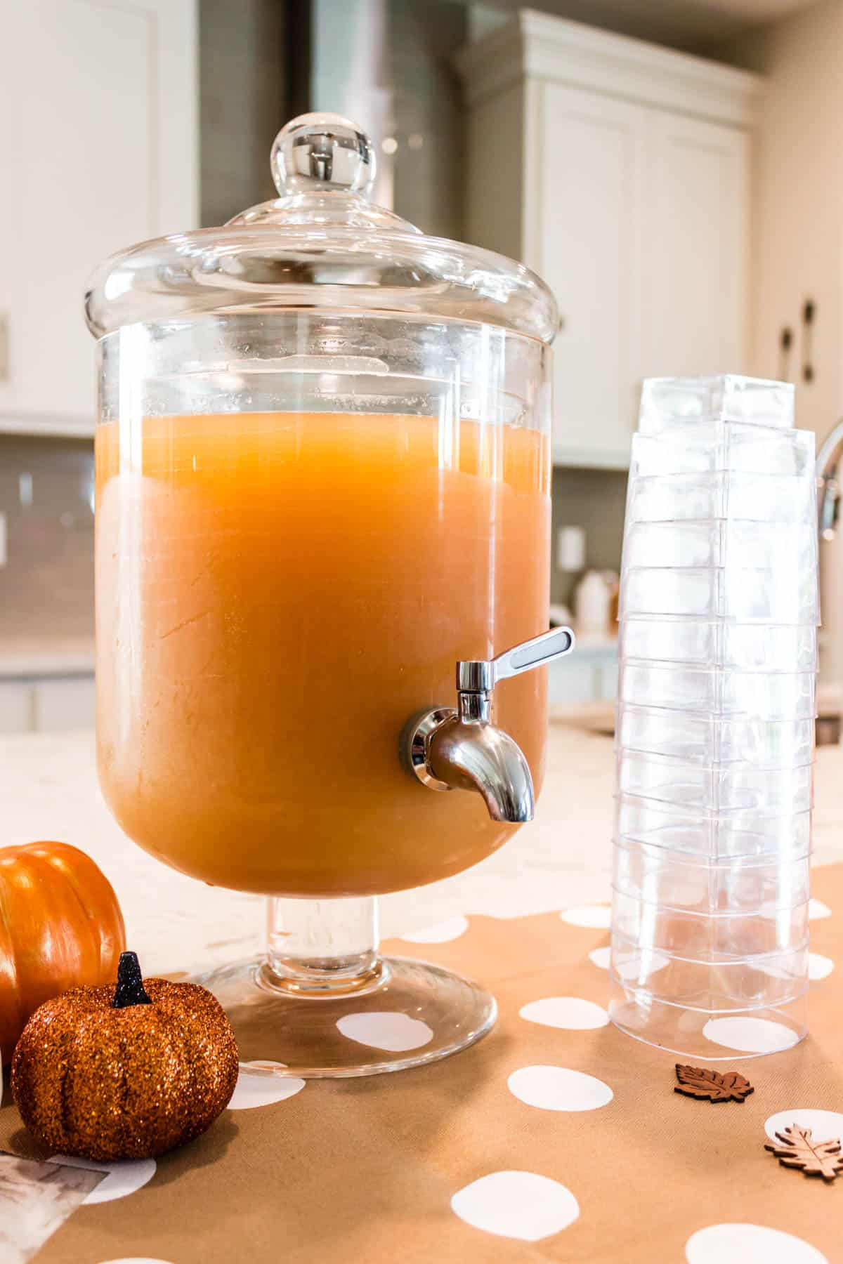 Apple cider punch in a glass beverage dispenser.