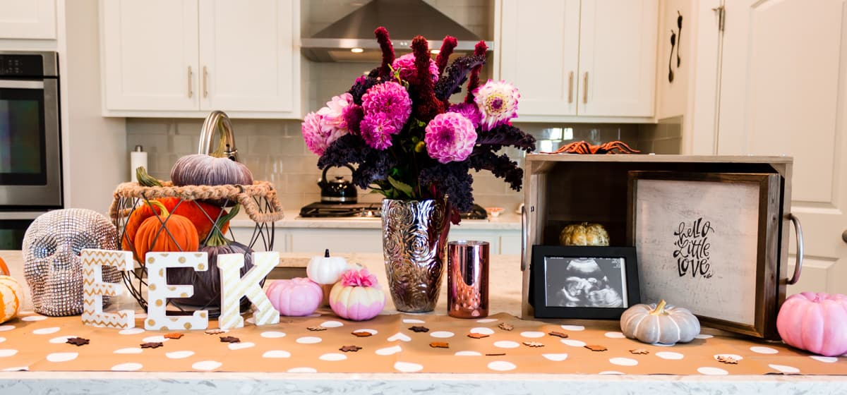 "Countertop decorated with mini pumpkins, ""EEK"" letters, and a beautiful pink banquet of fresh flowers."