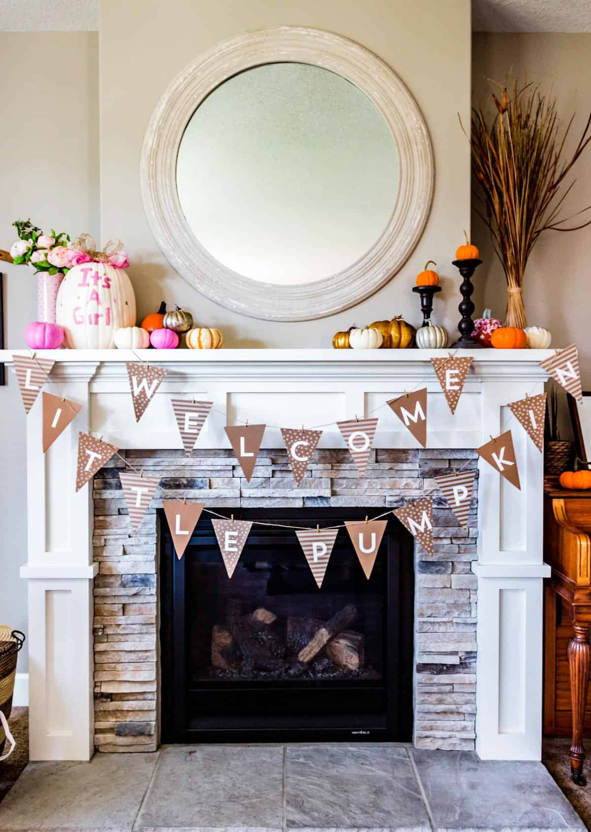 "A fireplace mantle decorated with a ""Welcome Little Pumpkin"" banner and an assortment of painted mini pumpkins in silver, gold, and pink mixed with natural orange and white mini pumpkins."