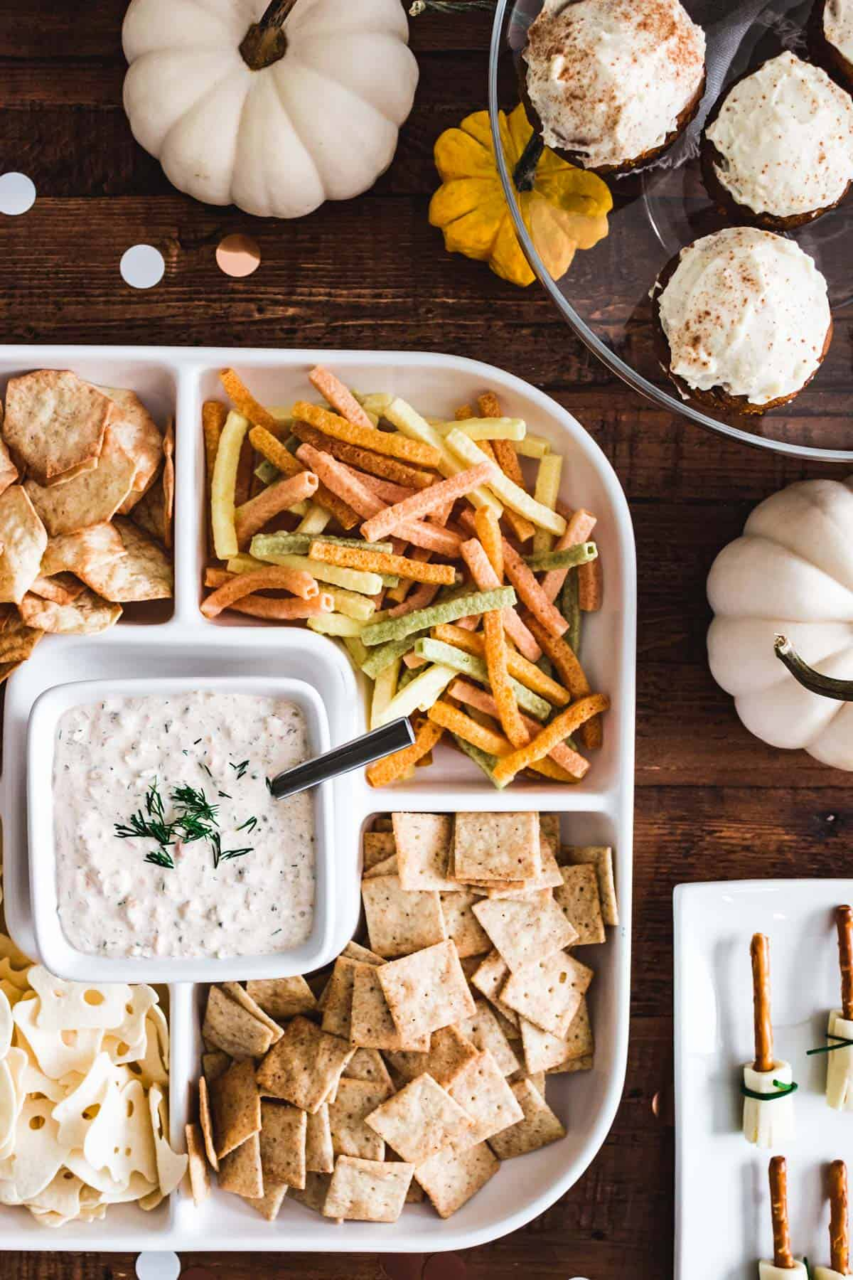 Smoked salmon dip with dill and capers served with an assortment of chips and crackers.