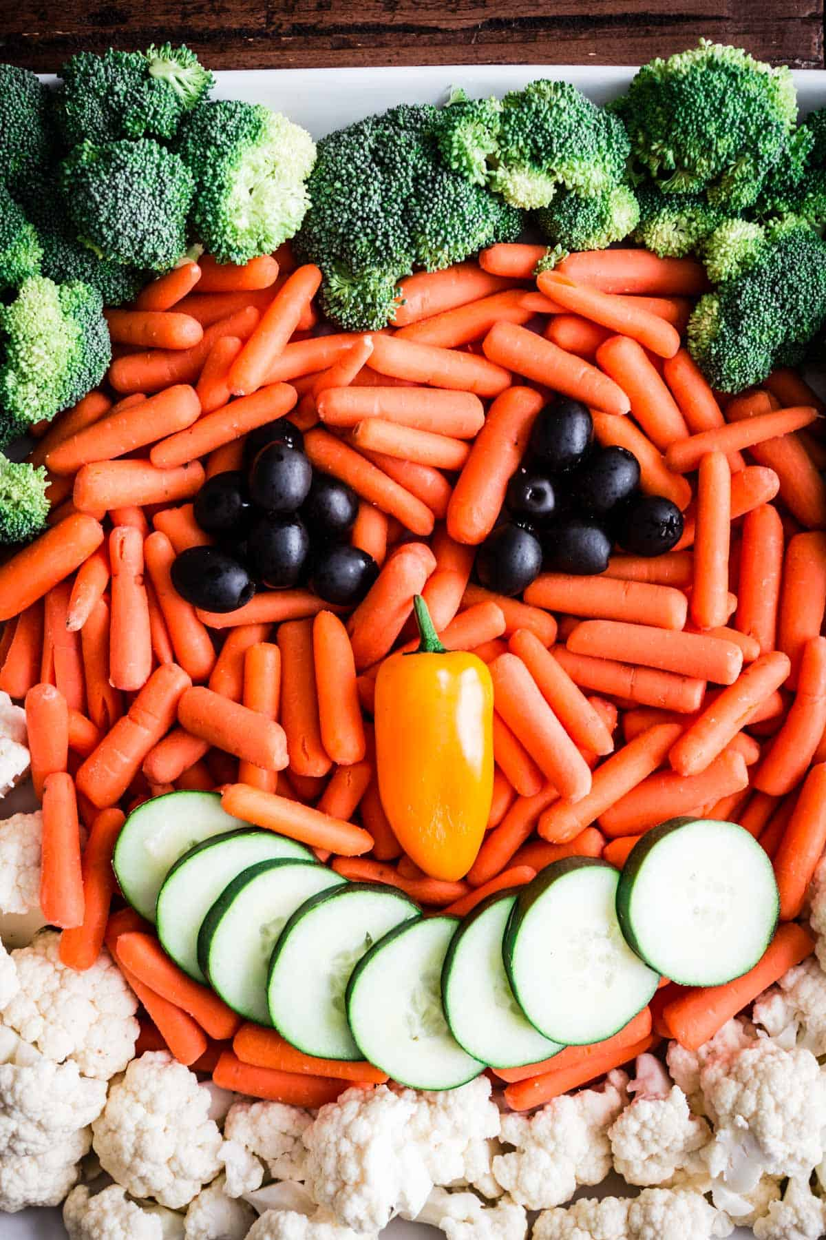 A veggie plate with mini carrots, cucumber, black olives, broccoli, cauliflower and a yellow pepper arranged to look like a smiling jack o'lantern.