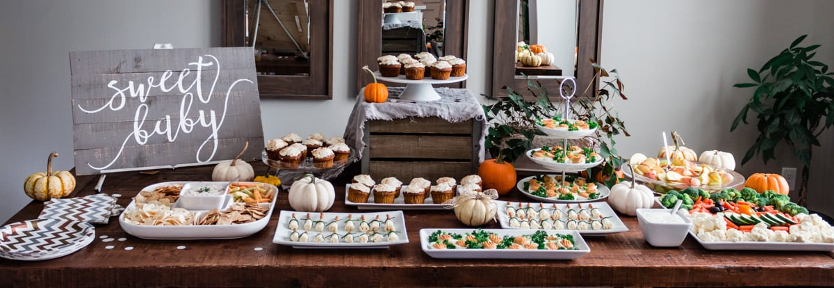 "Table arranged with fall themed party appetizers, mini pumpkins, and a ""Sweet Baby"" sign."
