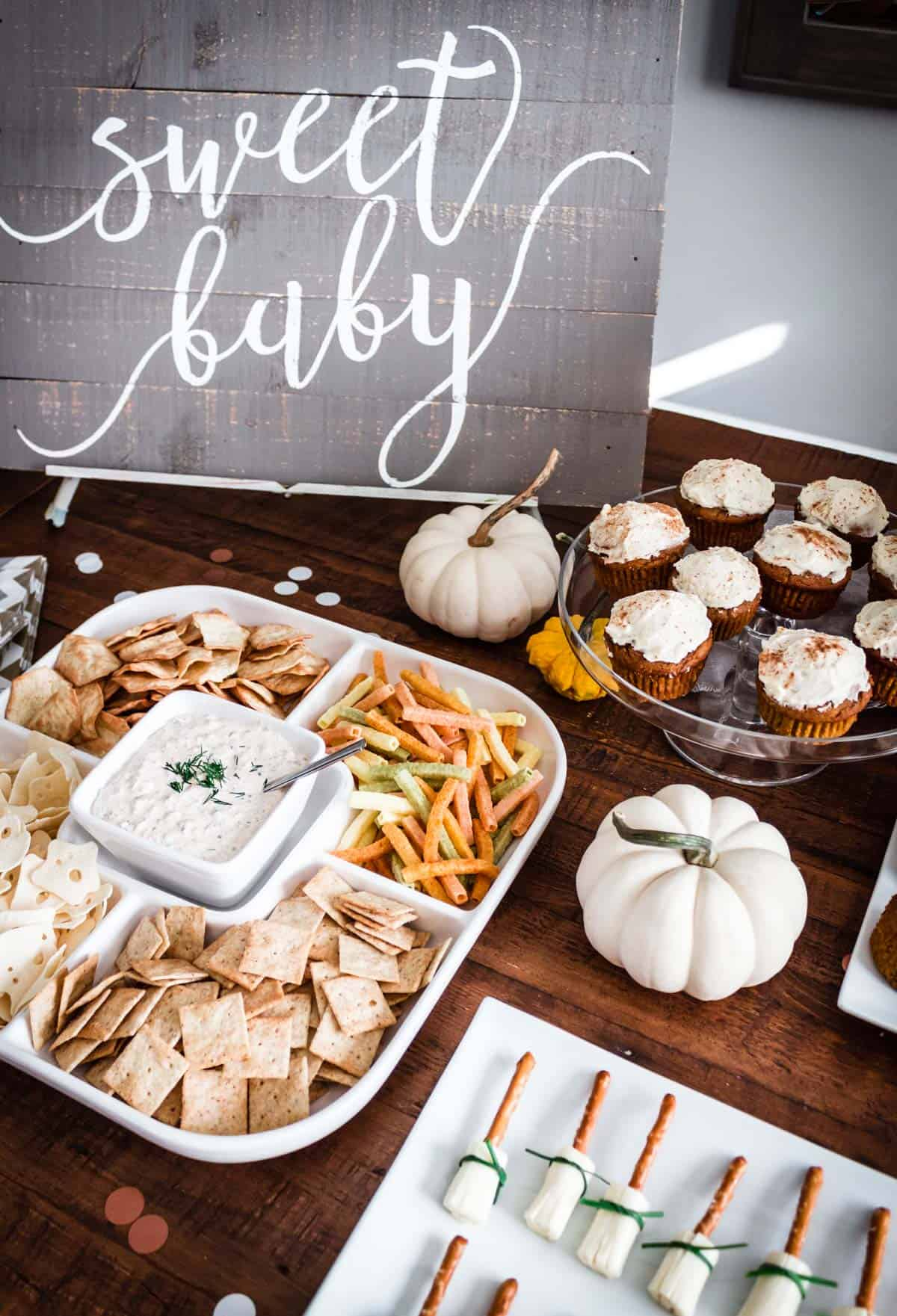 "A ""Sweet Baby"" sign sits next to fall themed party appetizers and several mini pumpkins."