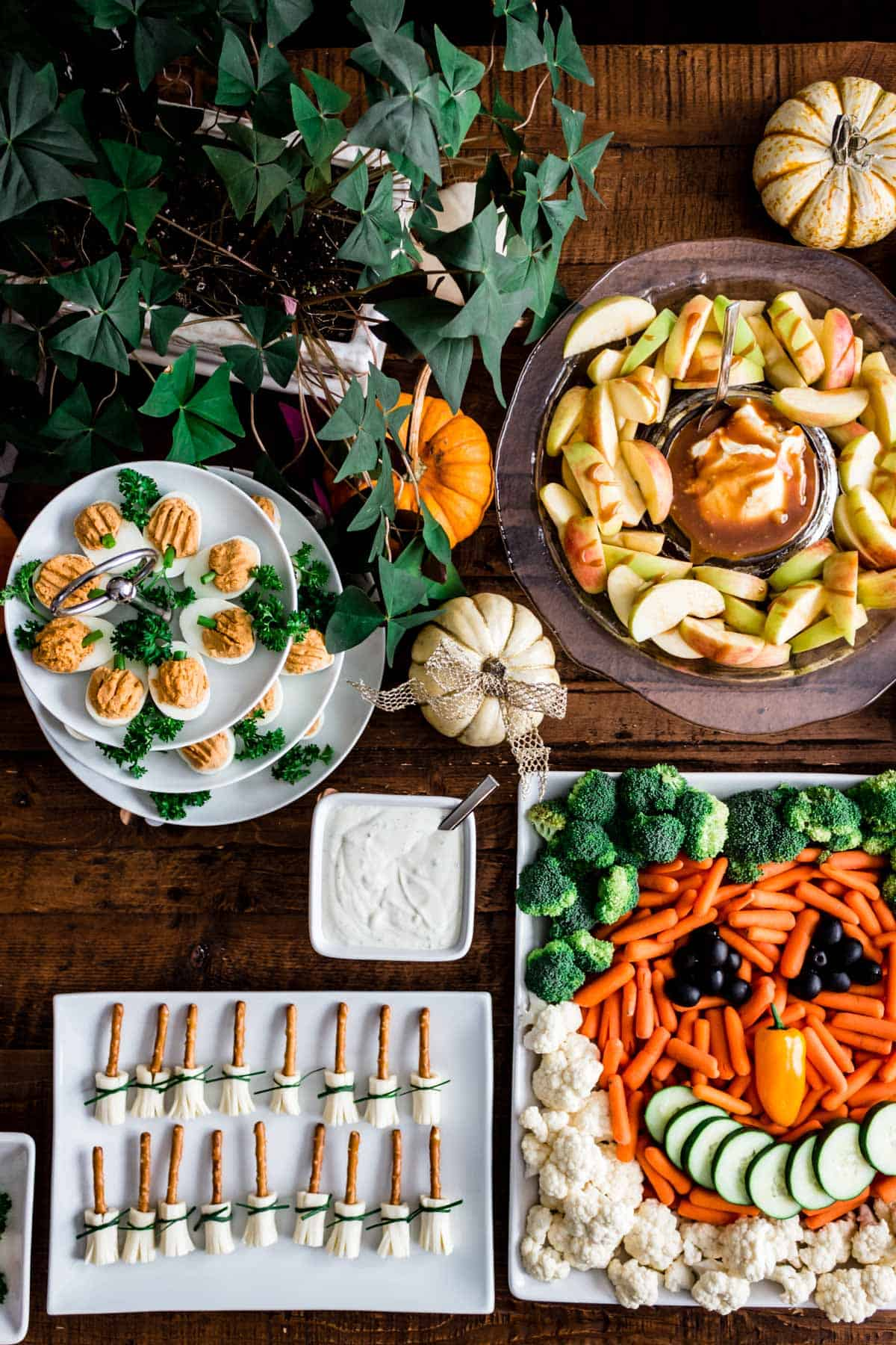 Fall themed appetizers and party foods arranged on a rustic wooden farmhouse style table.