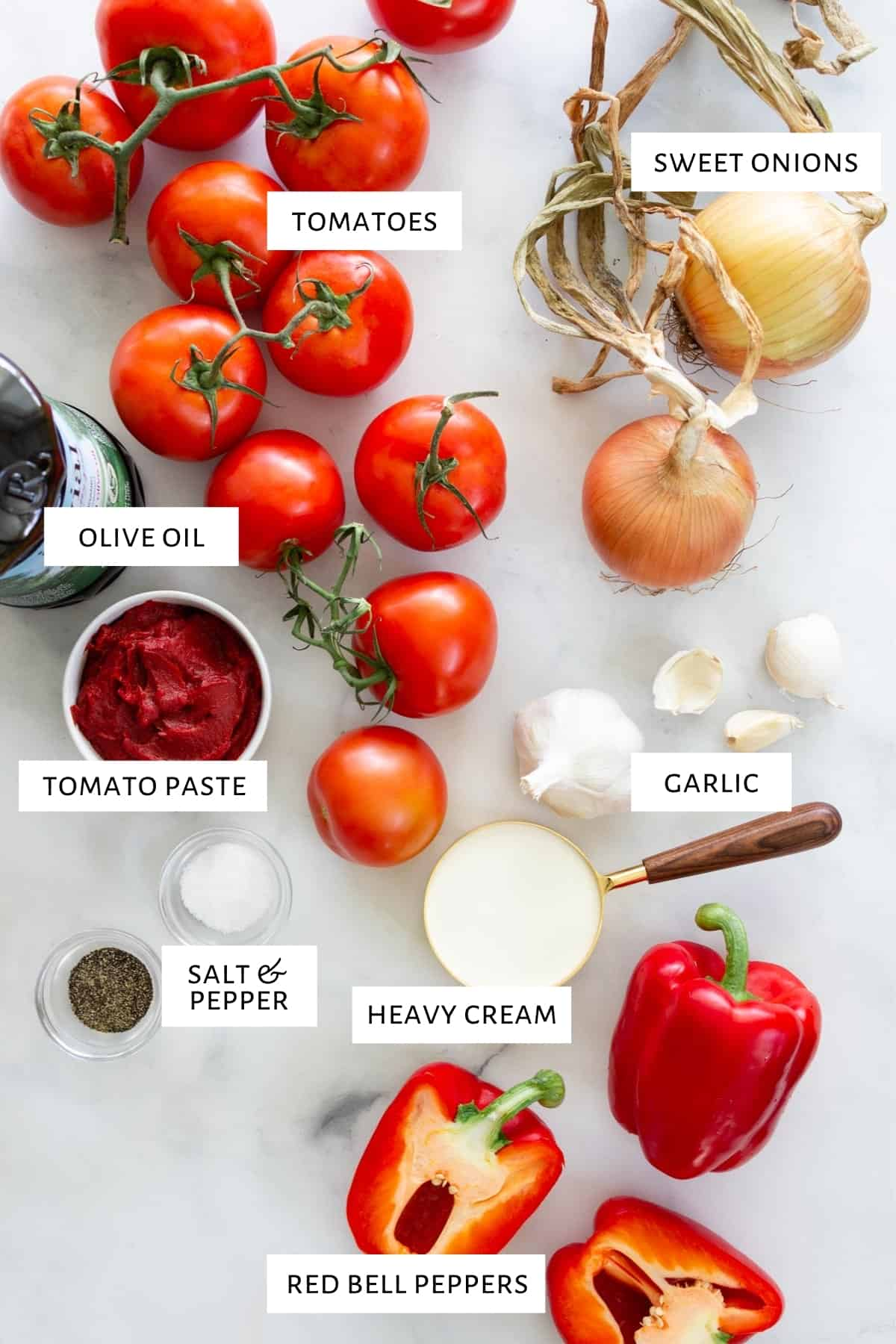 Ingredients to make roasted red pepper tomato basil soup are spread out on a marble countertop.