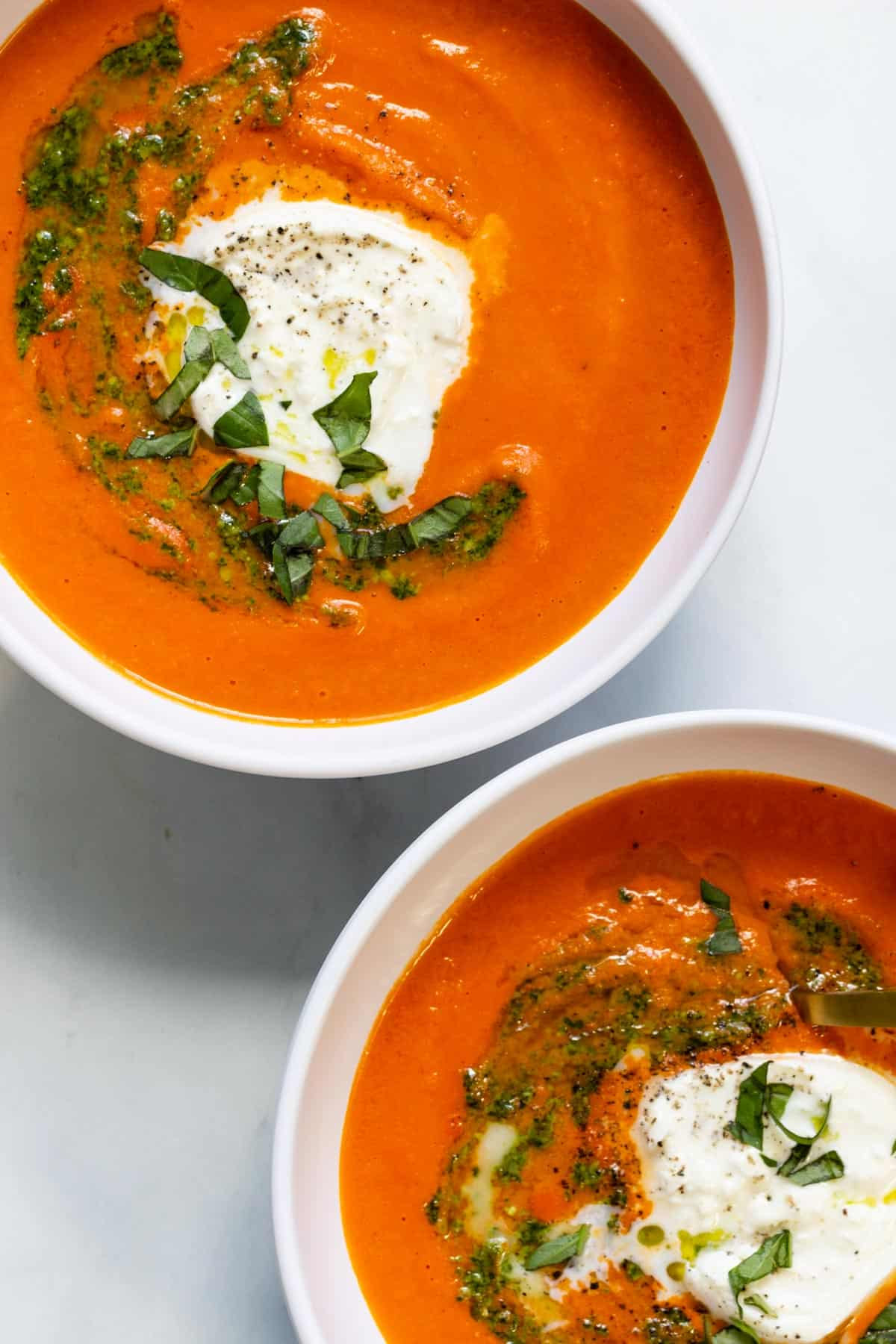 Two bowls of creamy roasted red pepper tomato basil soup topped with burrata and fresh basil.