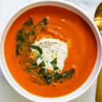 A white bowl of roasted red pepper tomato soup topped with burrata, basil, and a swirl of pesto.
