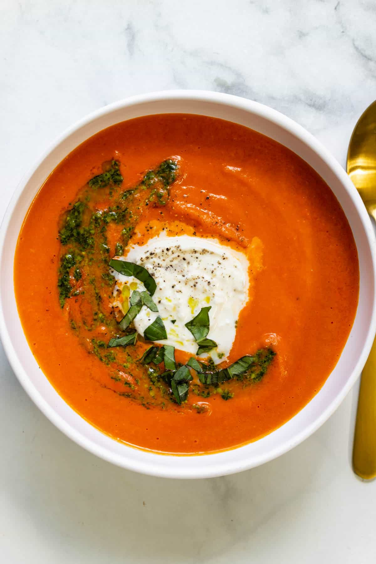 A white bowl of roasted red pepper tomato basil soup topped with burrata, fresh basil and a swirl of pesto. A gold spoon sits next to the bowl.