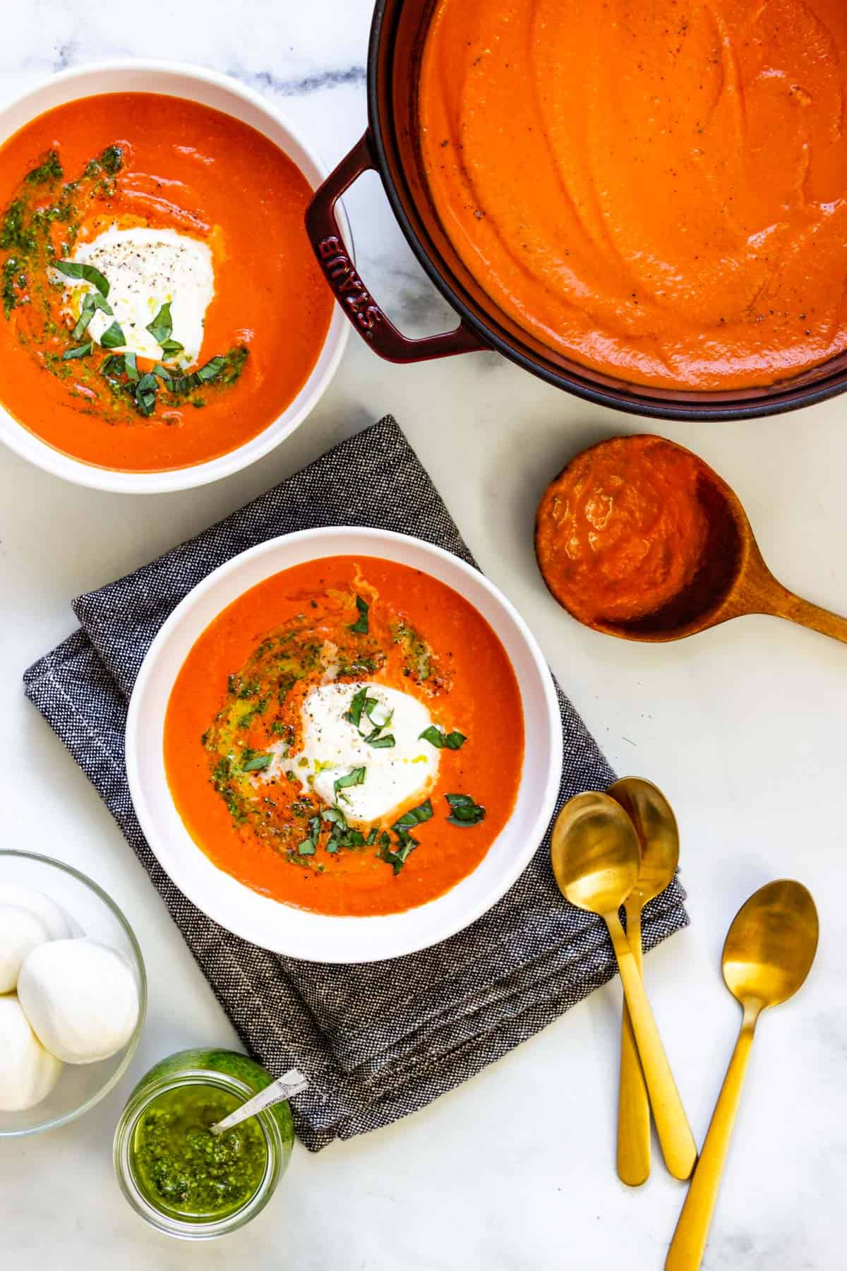 A pot of creamy red pepper tomato soup. Two bowls of soup, a bowl of burrata, and several gold spoons sit on the counter as well.