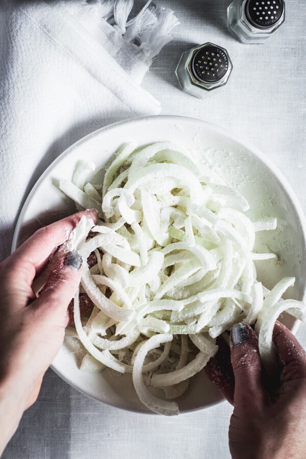 Two hands tossing thinly sliced onions in gluten free flour. Salt and pepper shakers sit nearby.