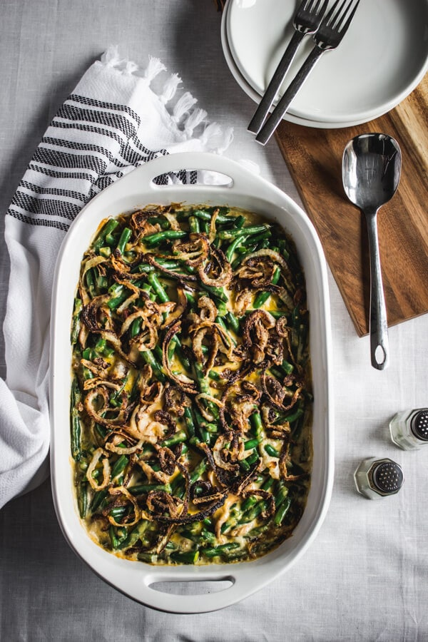 Gluten-free cheesy green bean casserole topped with crisp sautéed onion in a white baking dish. Salt and pepper shakers and a couple of forks and plates lay nearby.