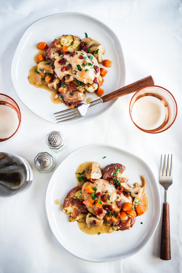 Two plates of chicken coq au vin blanc topped with crispy bacon pieces, carrots, mushrooms, and a tasty, white wine gravy-like sauce. Two rose colored glasses with a bottle of Riesling sit nearby.