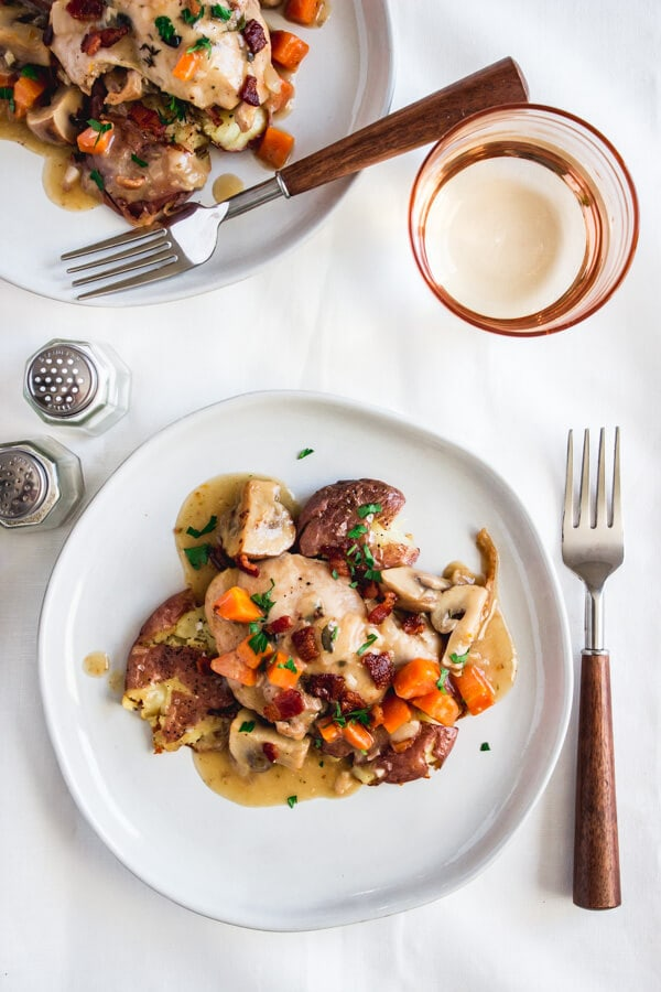 Two plates of chicken coq au vin blanc topped with crispy bacon pieces, carrots, mushrooms, and a tasty, white wine gravy-like sauce. A rose colored glass filled with Riesling sits nearby.