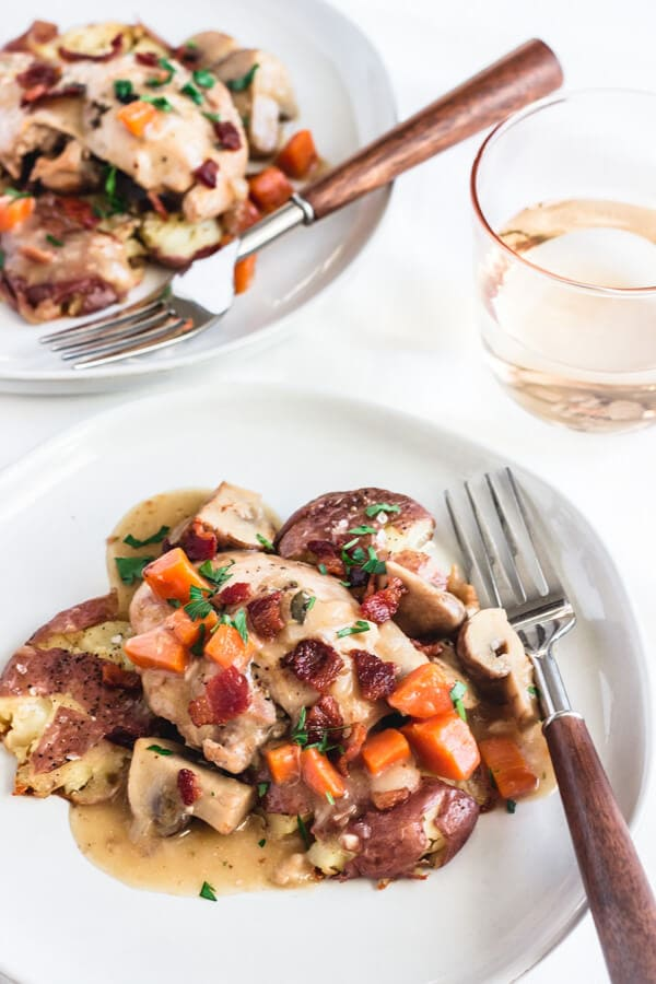 A close up view of chicken coq au vin blanc topped with crispy bacon pieces, carrots, mushrooms, and a tasty, white wine gravy-like sauce. Silver fork with a wooden handle rests on the plate.