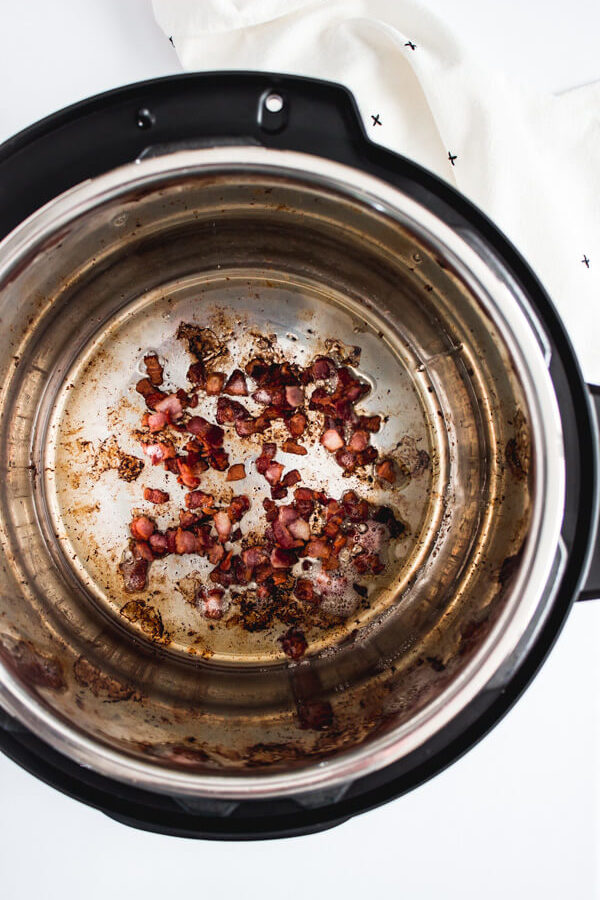 Chopped bacon sautéing in an Instant Pot.