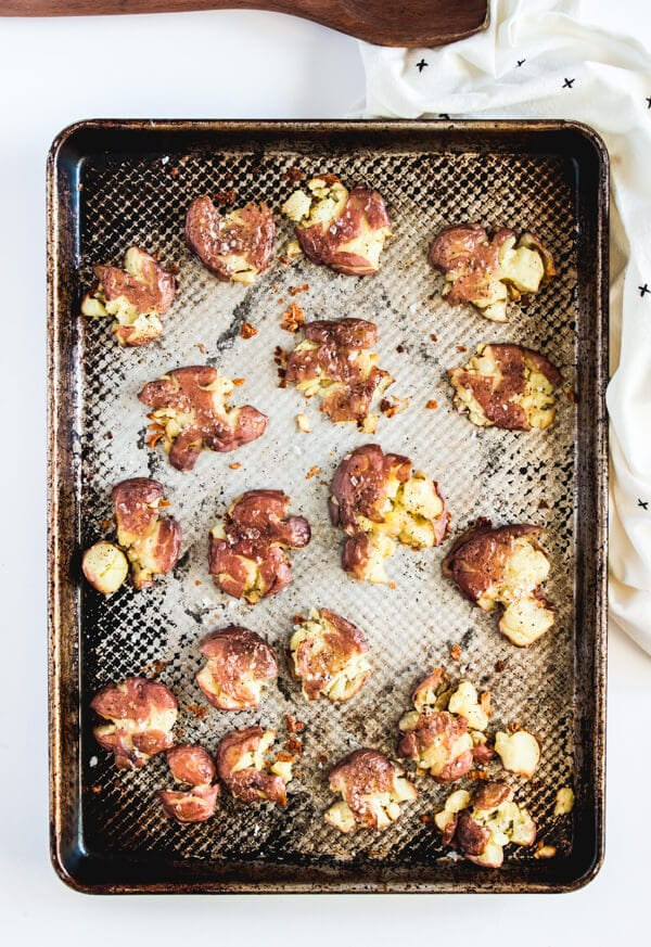 A baking sheet with crispy smashed baby red potatoes sprinkled with Maldon flaked sea salt.