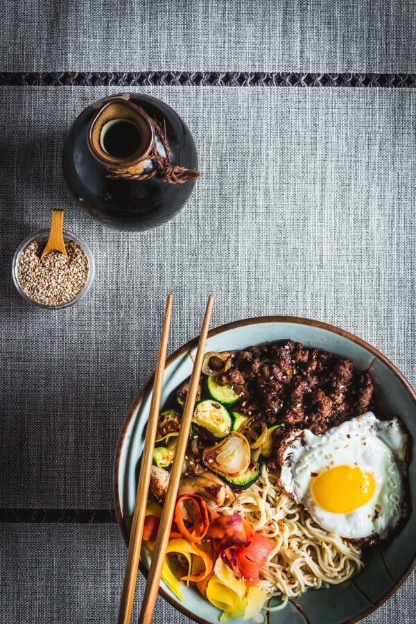 A bowl of tasty, gluten free bibimbap with savory ground beef, sautéed vegetables, gluten free rice ramen noodles, and a yolky fried egg! Two chopsticks rest side by side on top of the bowl.