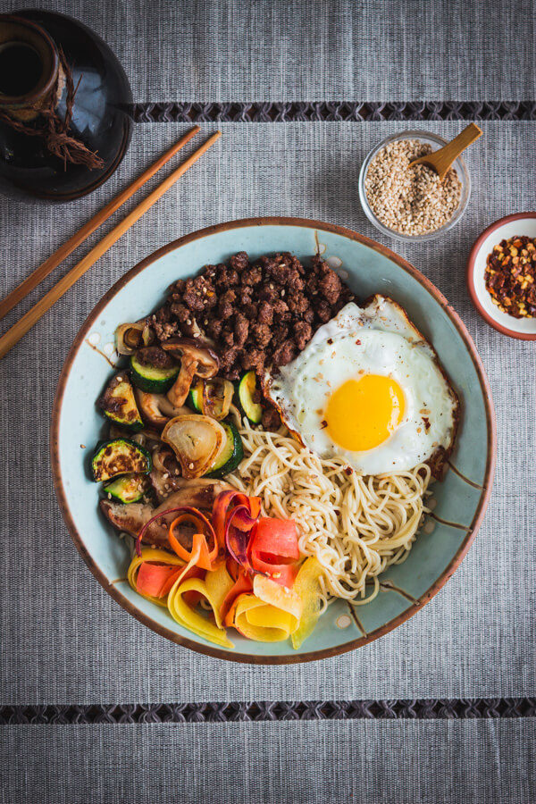 A bowl of tasty, gluten free bibimbap with savory ground beef, sautéed vegetables, gluten free rice ramen noodles, and a yolky fried egg!