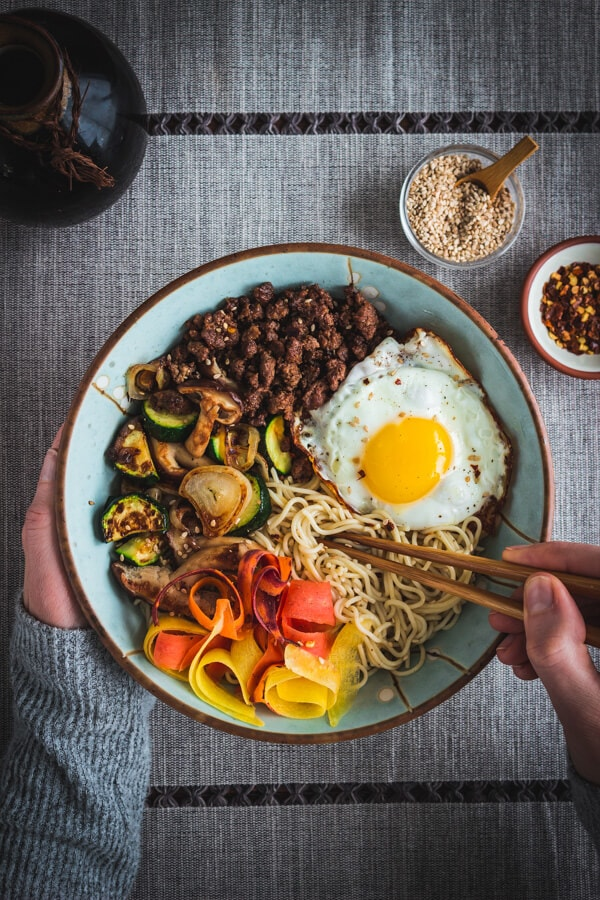 Two hands holding a pair of chopsticks and a bowl of tasty, gluten free bibimbap with savory ground beef, sautéed vegetables, gluten free rice ramen noodles, and a yolky fried egg! Toasted sesame seeds and crushed red chili are in pinch bowls nearby.