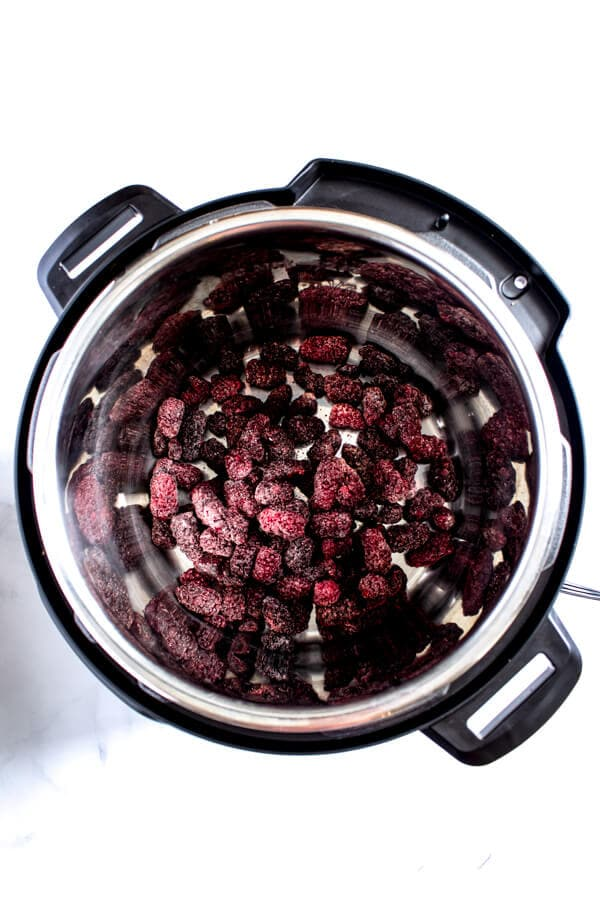 Four cups of frozen marionberries are added to an instant pot.