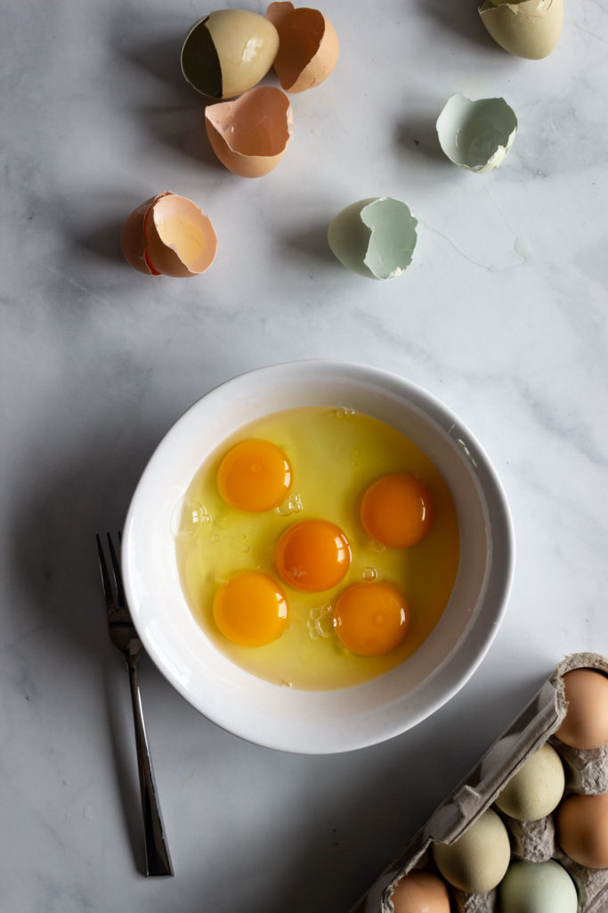 Cracked eggs in a white bowl. Eggs shells lay on the counter nearby.